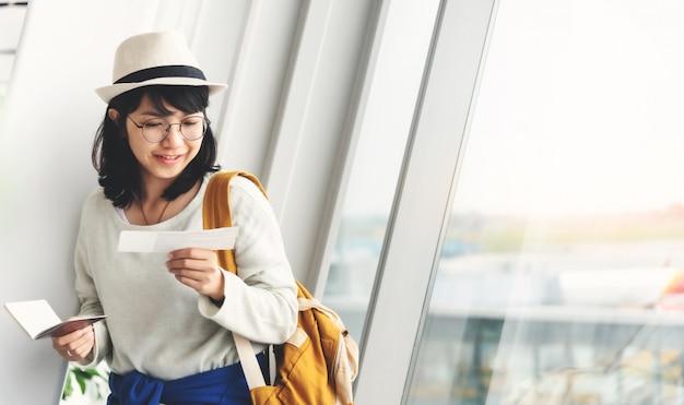 Mujer asiática joven feliz que sostiene su pasaporte y boleto cerca de la ventana del aeropuerto.