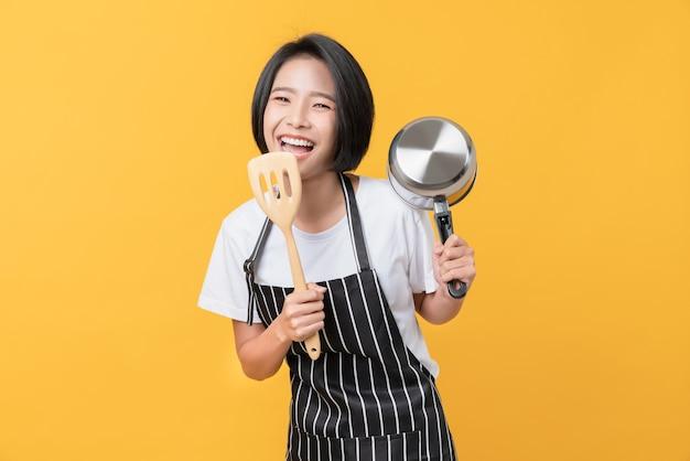 La mujer asiática joven feliz usa un delantal y muestra la espátula con la olla sobre fondo naranja claro.