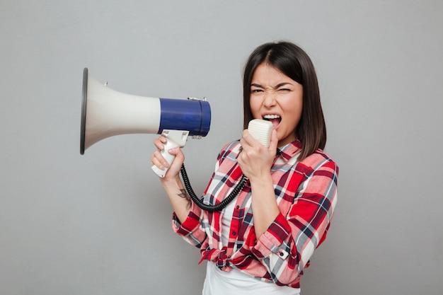 Mujer asiática joven de griterío que sostiene el altavoz.