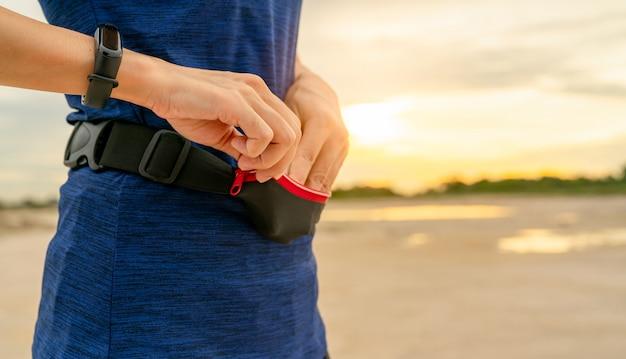 La mujer asiática joven guarda el teléfono inteligente en la bolsa de la cintura antes de ejecutar el ejercicio cardiovascular en la mañana.