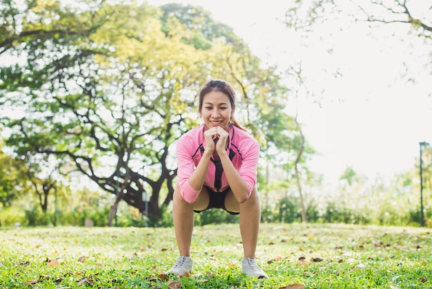 La mujer asiática joven hace posiciones en cuclillas para el ejercicio para construir su cuerpo de la belleza en parque