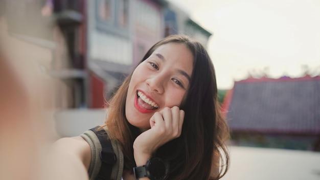 Mujer asiática joven hermosa alegre alegre del blogger del backpacker que usa el smartphone que toma el selfie
