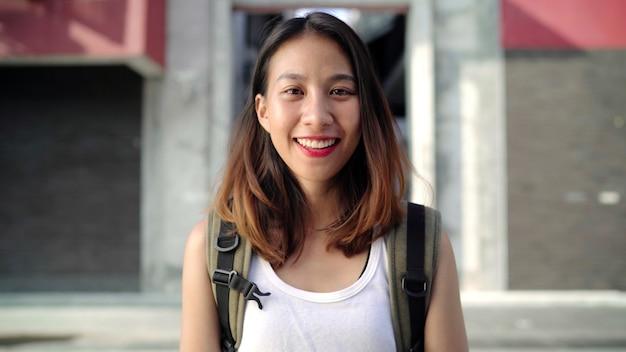 Mujer asiática joven hermosa alegre del backpacker que siente la sonrisa feliz a la cámara