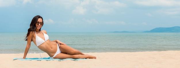 Mujer asiática joven hermosa en el bikini blanco en fondo de la bandera de la playa del verano