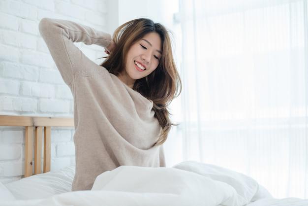 Mujer asiática joven hermosa feliz que despierta por la mañana, sentándose en la cama, estirando en dormitorio acogedor
