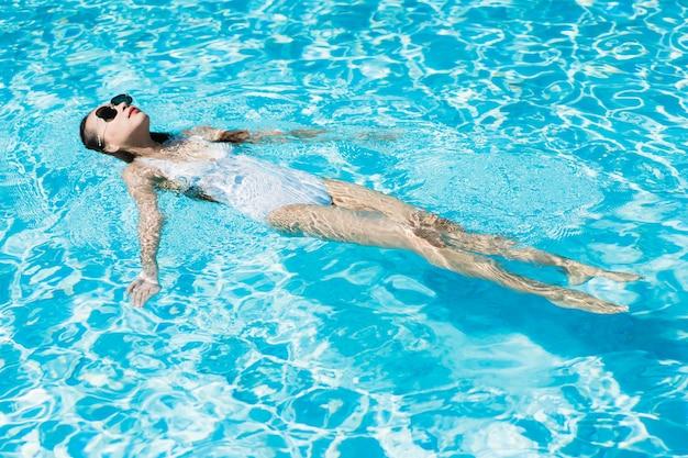 La mujer asiática joven hermosa feliz y la sonrisa en la piscina para relajan viaje y vacaciones