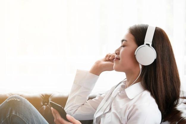Mujer asiática joven hermosa feliz de utilizar smartphone y escuchar música en los auriculares.