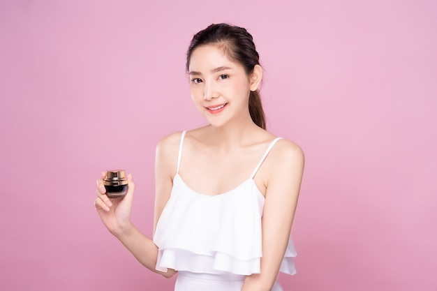 Mujer asiática joven hermosa con la piel blanca fresca limpia que sostiene el producto de la crema del tratamiento facial una mano con sonrisa.