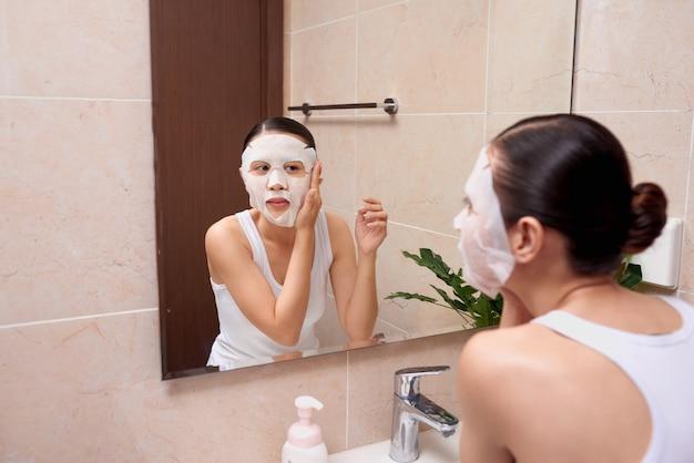 Mujer asiática joven hermosa que aplica la máscara facial cosmética en el baño.