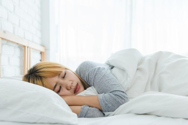 Mujer asiática joven hermosa que duerme en cama por la mañana