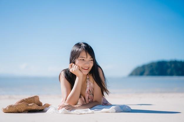 La mujer asiática joven hermosa que miente en feliz de la playa se relaja cerca del mar.