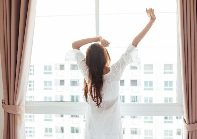 Mujer asiática joven hermosa que se sienta en cama y que estira por la mañana en el dormitorio.