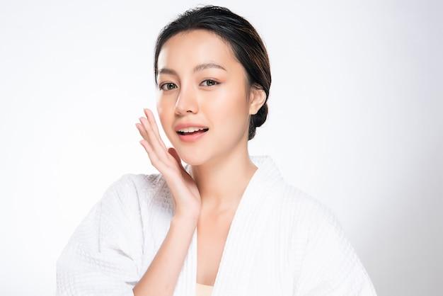 La mujer asiática joven hermosa que toca la mejilla suave y sonríe con la piel limpia y fresca. felicidad y alegría con, aislado en blanco, belleza y cosmética,