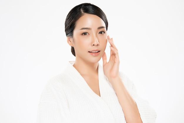 La mujer asiática joven hermosa que toca la mejilla suave y sonríe con la piel limpia y fresca. felicidad y alegría con el concepto de belleza y cosmética