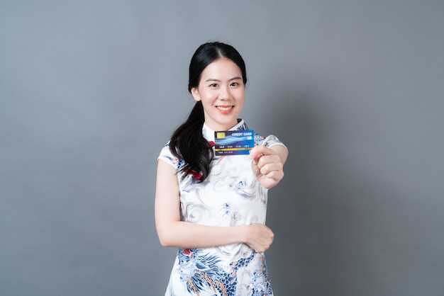 Mujer asiática joven hermosa que usa el vestido tradicional chino con la mano que sostiene la tarjeta de crédito en la pared gris