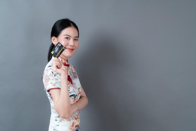 Mujer asiática joven hermosa que usa el vestido tradicional chino con la mano que sostiene la tarjeta de crédito