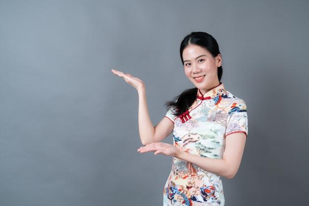 Mujer asiática joven hermosa que usa el vestido tradicional chino con la presentación de la mano