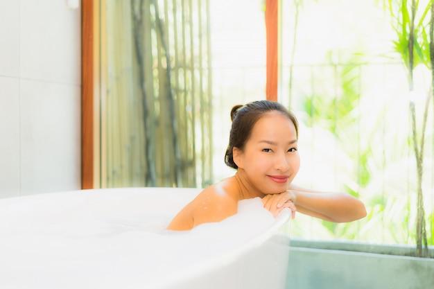 La mujer asiática joven hermosa del retrato en la bañera para toma un baño