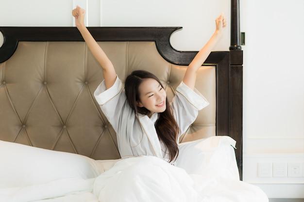 La mujer asiática joven hermosa del retrato despierta con feliz y sonríe en cama en interior del dormitorio