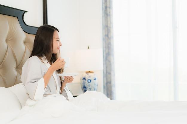 La mujer asiática joven hermosa del retrato despierta con sonrisa feliz y la taza de café en cama en el dormitorio inter