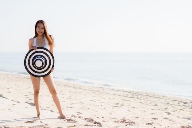 Mujer asiática joven hermosa del retrato feliz y sonrisa en el mar y el océano de la playa
