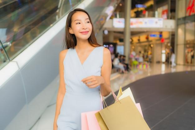 Mujer asiática joven hermosa del retrato feliz y sonrisa con el panier de los grandes almacenes