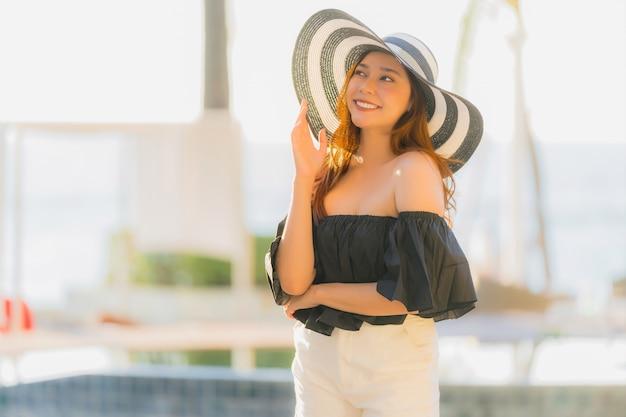Mujer asiática joven hermosa del retrato feliz y sonrisa con viaje en el mar y la playa neary del centro turístico del hotel
