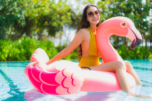 Mujer asiática joven hermosa del retrato en el flotador inflable del flamenco en piscina en el centro turístico del hotel