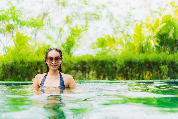 Mujer asiática joven hermosa del retrato en piscina alrededor del hotel y del centro turístico