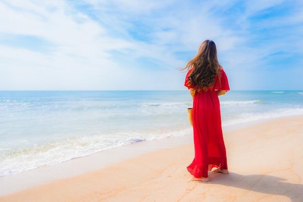 Mujer asiática joven hermosa del retrato en la playa y el mar