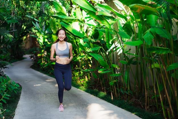 Mujer asiática joven hermosa del retrato que corre con feliz y sonrisa en el jardín