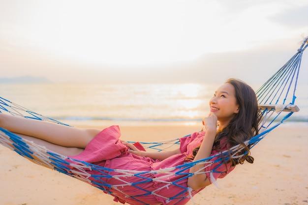 Mujer asiática joven hermosa del retrato que se sienta en la hamaca con el mar y el oce cercano felices de la playa de la sonrisa