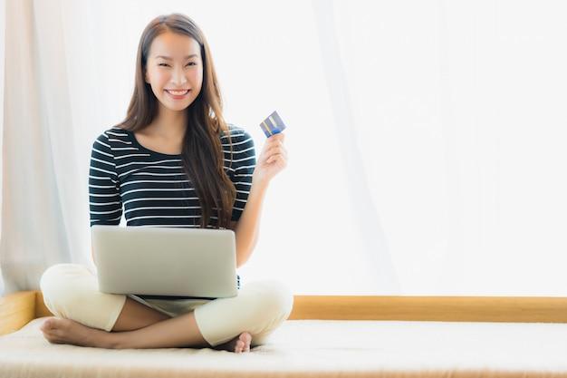 Mujer asiática joven hermosa del retrato que usa el cuaderno o el ordenador portátil del ordenador con la tarjeta de crédito para hacer compras