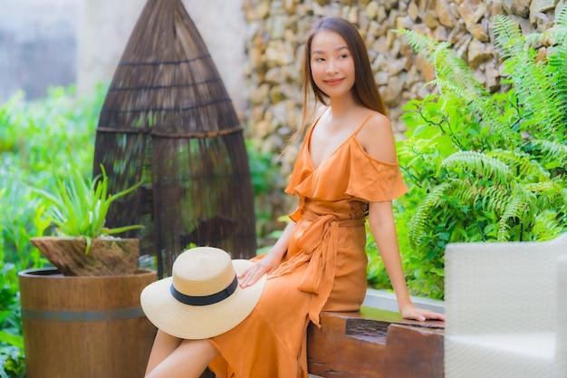 La mujer asiática joven hermosa del retrato se relaja en silla alrededor de jardín
