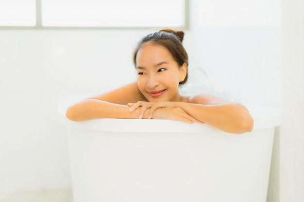 La mujer asiática joven hermosa del retrato toma una bañera en cuarto de baño