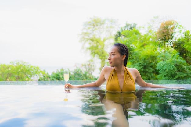 La mujer asiática joven hermosa del retrato con el vidrio del champán para relaja el ocio