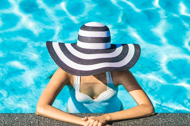 Mujer asiática joven hermosa con el sombrero en la piscina para el viaje y las vacaciones