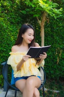 La mujer asiática joven lee el libro alrededor de la naturaleza del jardín al aire libre