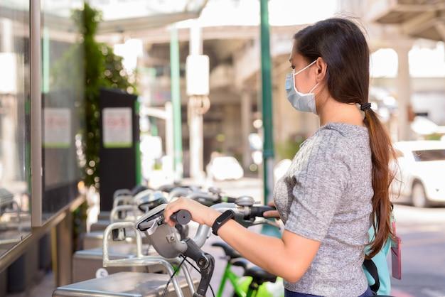 Mujer asiática joven con máscara de alquiler de bicicletas en la estación de servicio de bicicletas públicas