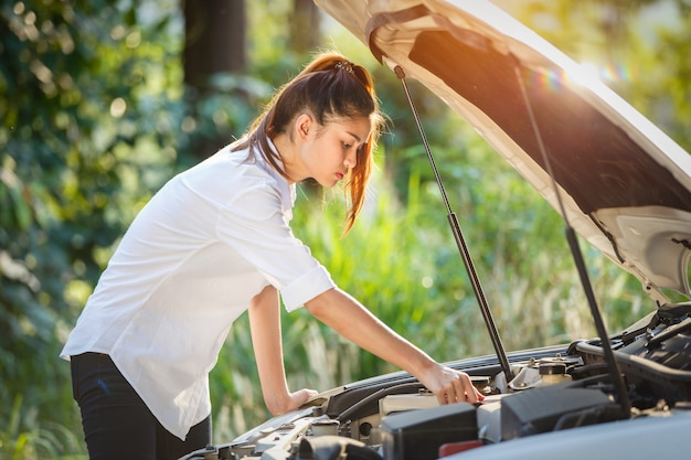 La mujer asiática joven mira debajo de la capilla de un coche quebrado.