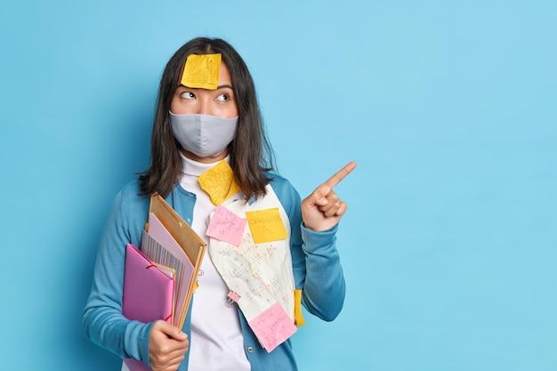 Mujer asiática joven morena pensativa trabaja desde casa durante el coronavirus en cuarentena
