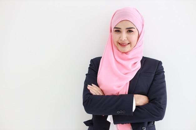 Mujer asiática joven musulmán hermosa que lleva la sonrisa azul del traje confiada.