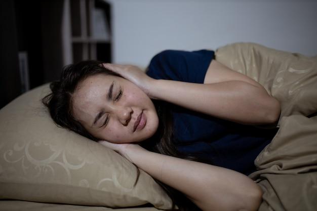La mujer asiática joven no puede dormir el insomnio a altas horas de la noche. no puedo dormir. apnea del sueño o estrés. concepto de trastorno del sueño.