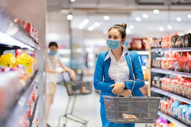 Mujer asiática joven en oficina uniforme con máscara protectora y compra de comestibles en el supermercado. concepto de prevención del virus covid-19.