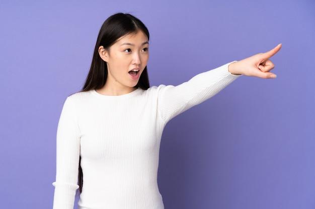 Mujer asiática joven en la pared púrpura que señala lejos