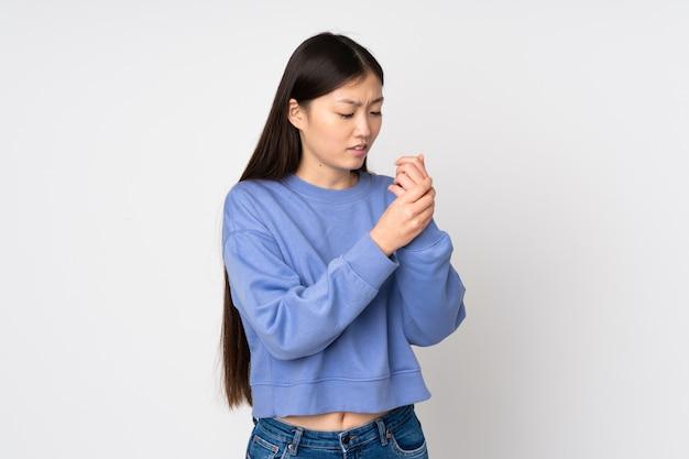 Mujer asiática joven en la pared que sufre de dolor en las manos