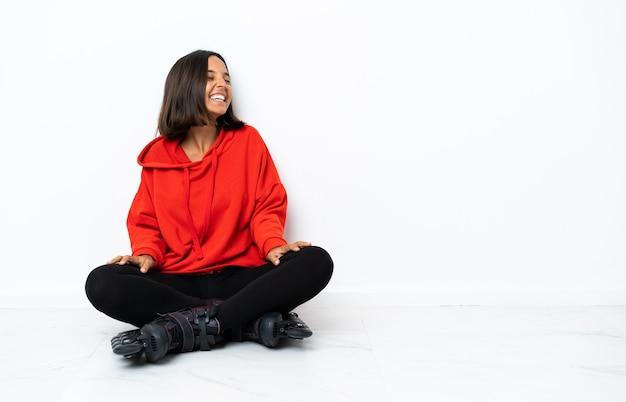 Mujer asiática joven con patines en el suelo riendo