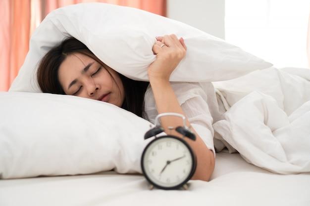 Mujer asiática joven perezosa que despierta en la madrugada para el trabajo diario rutinario.