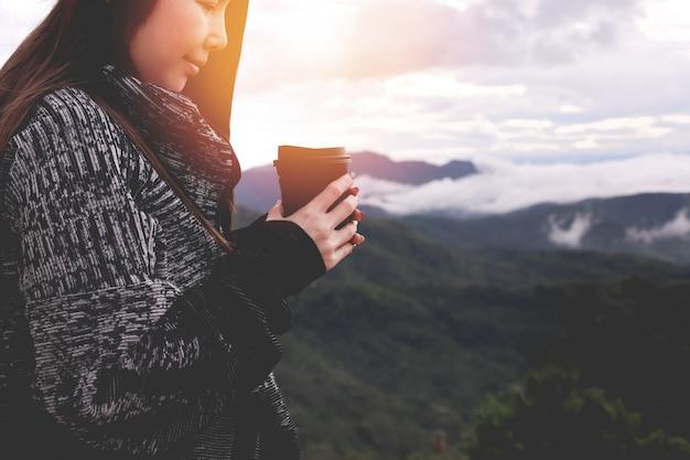 Mujer asiática joven que bebe el café caliente en la opinión del paisaje por mañana del invierno.