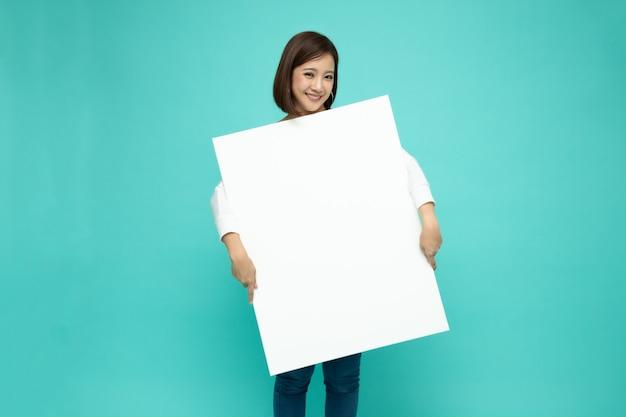 Mujer asiática joven que celebra la sonrisa y el papel grande blanco.